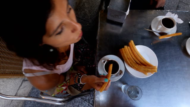 eating the famous churros breakfast in a cafe at the south of spain - churro stock videos & royalty-free footage
