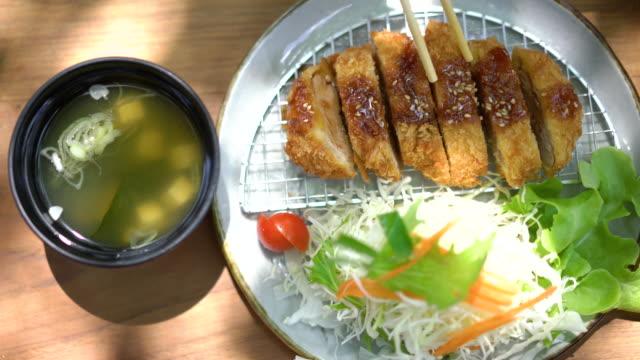 vidéos et rushes de manger du tonkatsu (porc frit) avec des baguettes - bol à soupe
