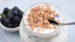 Eating yogurt with granola and berries in jar