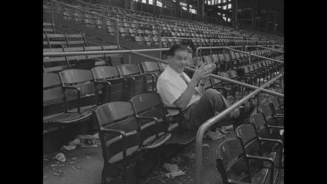 Ebbets Field in Brooklyn NY / empty stands in stadium / VS baseball fan George Fineman of Paramount News sits by himself in empty stands listens to...