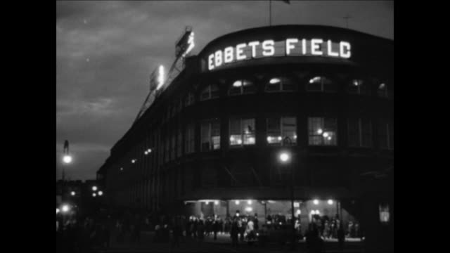 Ebbets Field w/ lights on people fans walking toward into stadium HA TD People entering baseball stadium crowded area w/ brick columns TU WS Back of...