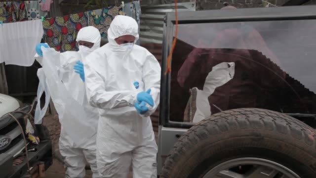 vídeos de stock, filmes e b-roll de ebola body collection team in monrovia liberia puts on ppe hazmat suits and sprays the house of a deceased ebola case down with chlorine before... - ébola