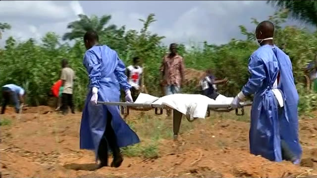 vídeos y material grabado en eventos de stock de ebola outbreak attempts to improve burial processes sierra men wearing protective gowns and masks carrying body on stretcher with people digging... - ébola