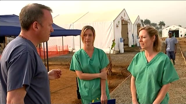ebola outbreak british doctors and nurses describe the care situation sierra leone makeni ext various shots uk medical staff under tent canopy as... - wife carrying stock videos and b-roll footage
