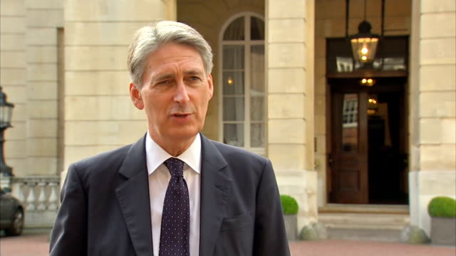 'Defeating Ebola in Sierra Leone' conference in London interviews ENGLAND London Lancaster House EXT Philip Hammond MP along and into building/...