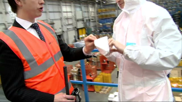 'enhanced screening' introduced at uk airports england hull int high angle gv ebola protective suit distribution centre factory floor with staff at... - sun visor stock videos and b-roll footage