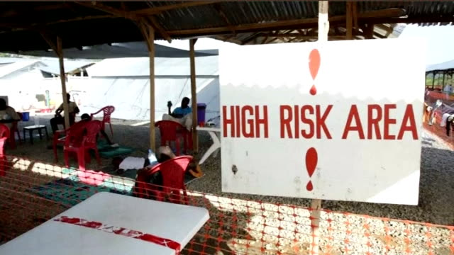 vidéos et rushes de first team of nhs volunteers boards flight to sierra leone t10111448 / tx sign 'high risk area' argus int royal navy crew members working at laptop... - épidémie