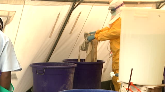 vídeos y material grabado en eventos de stock de medecins sans frontieres ebola clinic in conakry various of workers in protective clothing being disinfected after leaving the area of the compound... - ébola