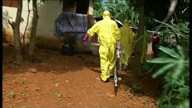 Ebola outbreak Red Cross burial team collects dead bodies Various shots of man spraying disinfectant at Red Cross worker in protective suit David Don...