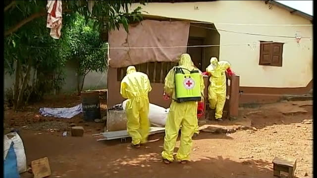 ebola outbreak threat of intervention at hospital set up by british government tx red cross workers in hazmat suits carry covered body of ebola... - dead person stock videos & royalty-free footage