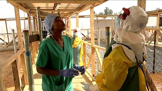 vídeos y material grabado en eventos de stock de ebola outbreak volunteers continue difficult and potentially deadly work in makeni sierra leone int tent medical volunteers putting on protective... - ébola