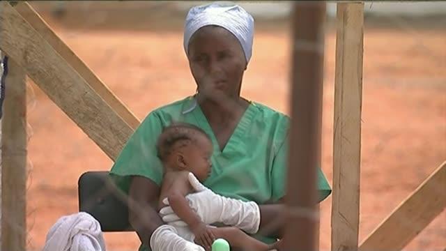vídeos y material grabado en eventos de stock de ebola virus vaccine successfully tested in guinea 512015 / t05011530 medical workers in protective suits carrying body of ebola victim alogn on... - ébola