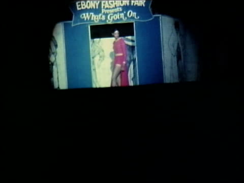 "ebony fashion fair presents, ""what's goin' on"", a fashion show created by ebony magazine / woman modeling red dress with long split panel in front /... - ブランド名点の映像素材/bロール"