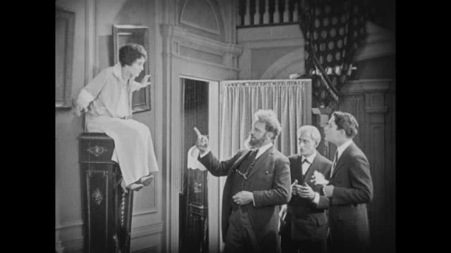 1925 eccentric man places questioning woman on top of pedestal - 1925 stock videos & royalty-free footage
