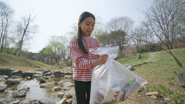 echo campaign - child picking up garbage by brook - ゴミ袋点の映像素材/bロール