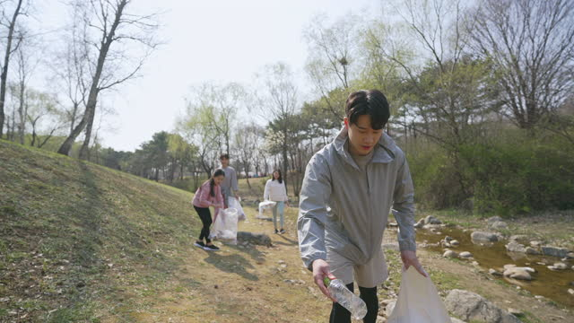 echo campaign - young man, women and child picking up garbage and walking in park - ゴミ袋点の映像素材/bロール