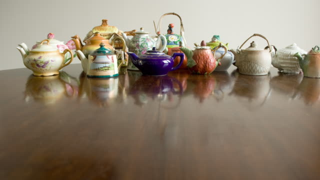 composite, eclectic teapot collection appearing on table - antik bildbanksvideor och videomaterial från bakom kulisserna