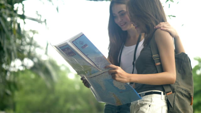 eco tourism : 2 young woman explorer looking at map - eco tourism stock videos & royalty-free footage