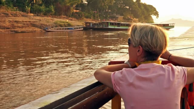 eco tourist female photographer on mekong river boat sunset cruise, laos - one mid adult woman only stock videos & royalty-free footage