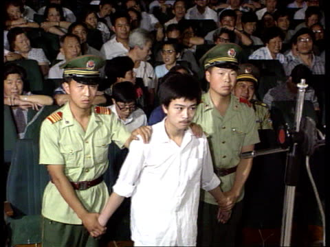 Economic reforms BOUGHT FROM EX SHANGHAI TV INT TMS Men accused of corruption being led along by police at show trial LAGV Show trial taking place MS...