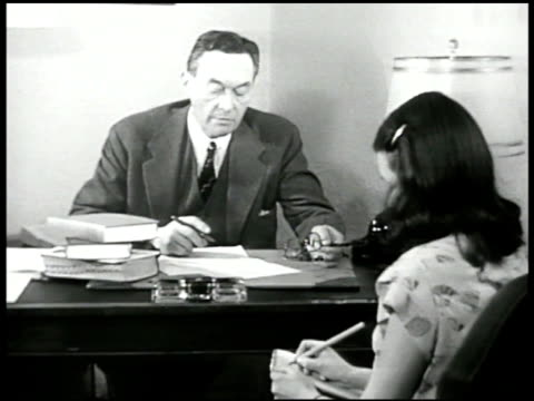 Economist Walter Lippmann at desk dictating to assistant 'the postwar difficulties are appearing faster than solutions our own position highly...