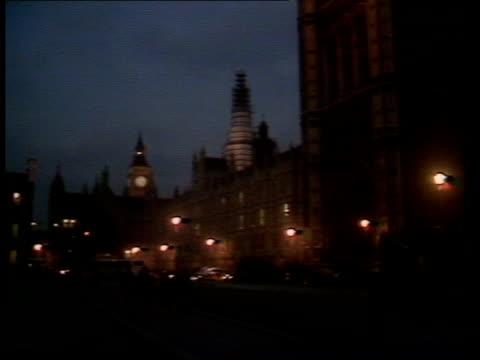 Autumn Financial Statement ENGLAND London Houses of Parliament GV Houses of Parliament as street lights blazing MS Light shining from upper storey...