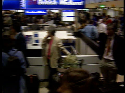 Economy class syndrome LIB London Heathrow Airport INT Passengers queuing at checkin desks PAN Passengers along thru airport terminal