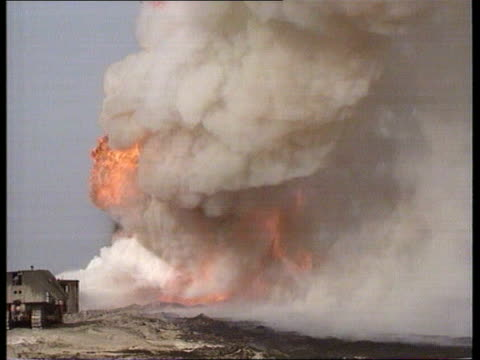 Kuwait oil wells MS Oil well blazing CMS Flames of the fire MS Water being squirted at the bottom of the flames CMS Fireman firing water jet TRACK...