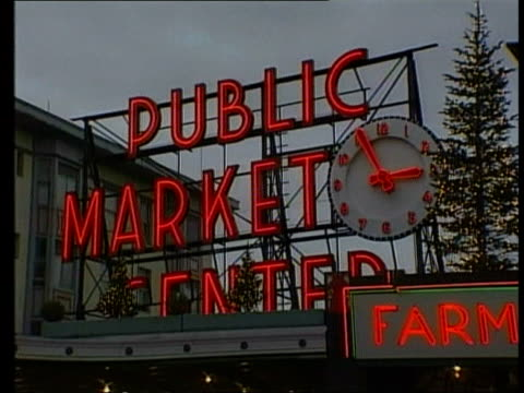 world trade organisation: us vs eu; itn usa: seattle: ext tgv skyline of seattle cms man in street playing saw name 'public market center' over... - street name sign stock-videos und b-roll-filmmaterial