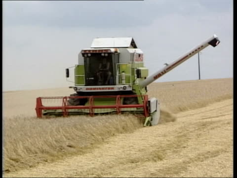 vídeos de stock e filmes b-roll de to reform cap; itn france ext farmer talking with driver of combine harvester farmer interview sot - changes to common agricultural policy will lead... - european union coin