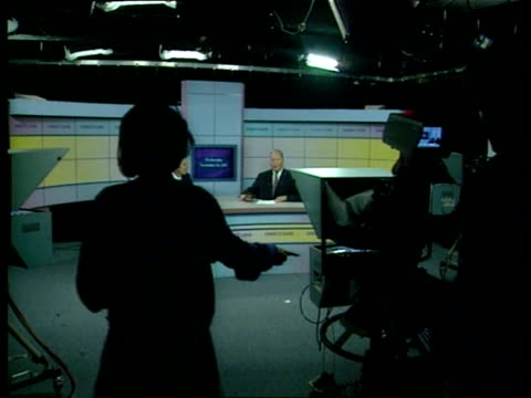 vídeos de stock, filmes e b-roll de budget crisis itn studio ms tv camera with politician in the viewer bv floor manager as she counts in host of programme politician guest ext ls right... - câmera de televisão
