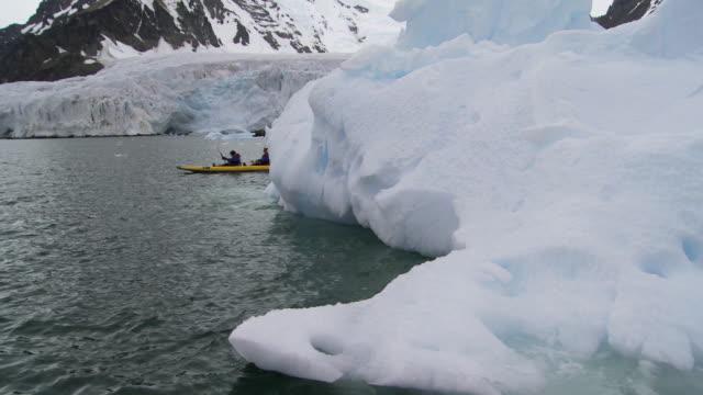 POV Eco-tourists in National Geographic Explorer kayak passing by iceberg / Marguerite Bay, Antarctic Peninsula, Antarctica