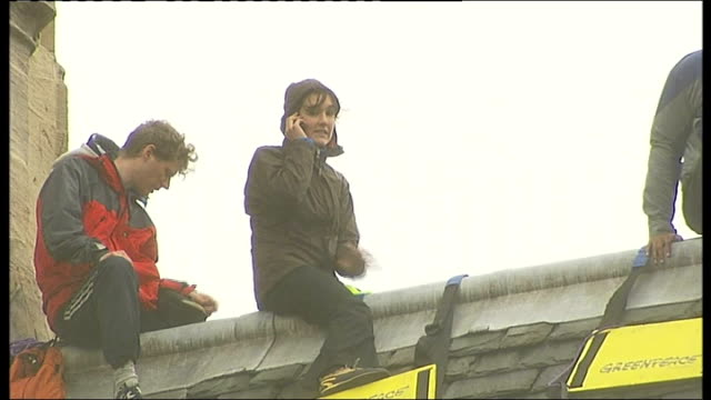 ecowarriors straddling roof protesters on roof pulling ladder up anita jones interview as speaking on mobile phone from roof sot we let police know... - legs apart stock videos and b-roll footage