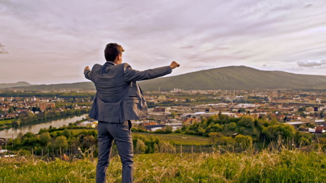 slo mo ecstatic businessman on the hill - punching the air stock videos & royalty-free footage