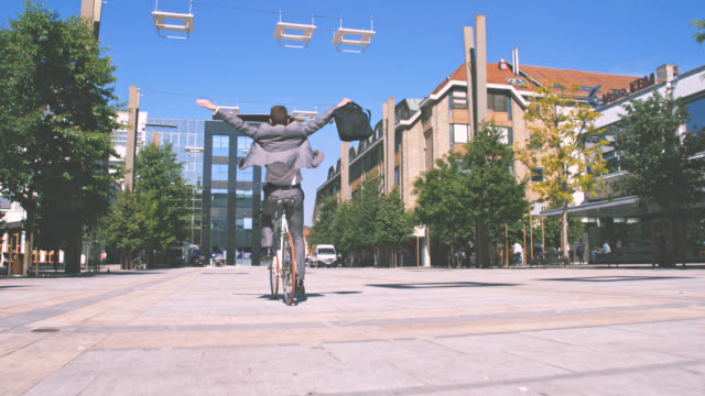 slo mo ecstatic businessman riding his bike with no hands - arms outstretched stock videos and b-roll footage