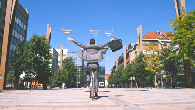 SLO MO Ecstatic businessman riding his bike without hands