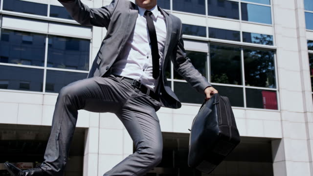 slo mo ecstatic businessman walking out of an office - jumping stock videos & royalty-free footage
