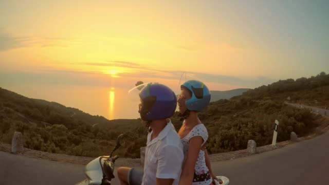 POV Ecstatic couple riding a scooter at sunset