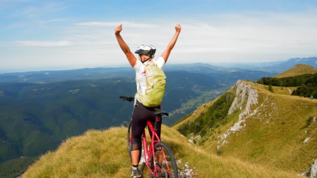 vídeos y material grabado en eventos de stock de slo mo ciclista mujer extática levantando los brazos en la alegría en el borde del precipicio - brazos estirados
