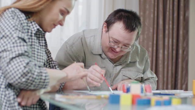 ecstatic man with down syndrome and smiling young woman painting with gouache together - gouache stock videos & royalty-free footage