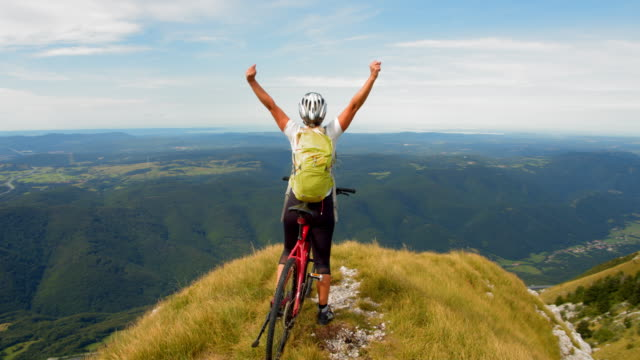 slo mo ecstatic mountain biker raising her arms in joy - arms raised stock videos & royalty-free footage