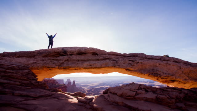 WS Ecstatic trekker walking on a sandstone arch