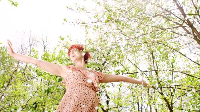 slo, mo, verzückt frau tanzen unter blütenblätter fallen - blütenblatt stock-videos und b-roll-filmmaterial