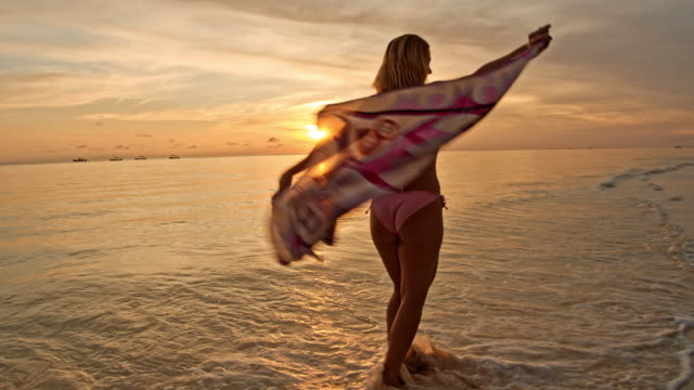 slo mo ecstatic woman holding a sarong while spinning on a tropical beach - sarong stock videos & royalty-free footage