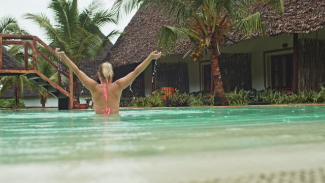 slo mo ecstatic woman in a swimming pool while it's raining - human limb stock videos & royalty-free footage