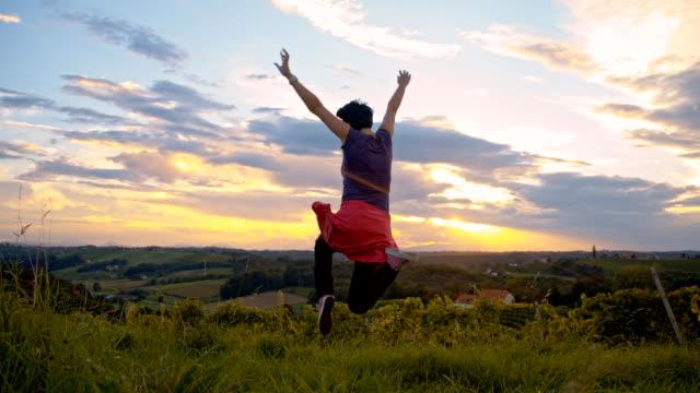 slo mo ecstatic woman jumping - human limb stock videos & royalty-free footage