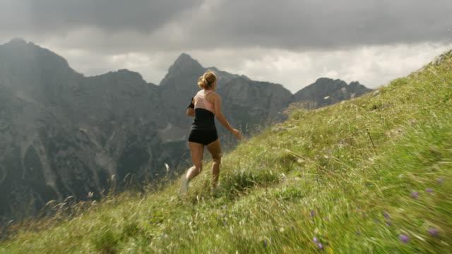 stockvideo's en b-roll-footage met slo mo extatische vrouw op de top van een berg - julian alps