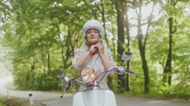 vidéos et rushes de femme extatique de ws prête pour un tour sur un scooter - casque de protection au sport