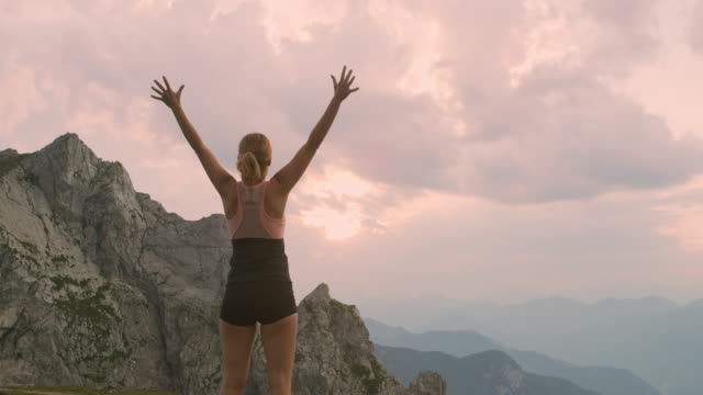 slo mo ecstatic woman running on the top of a mountain - punching the air stock videos & royalty-free footage