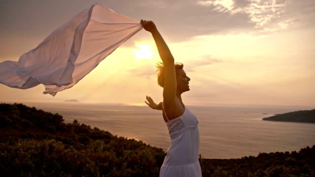 vídeos de stock e filmes b-roll de slo mo eufórico mulher apavorada em o vento - penhasco caraterísticas do território